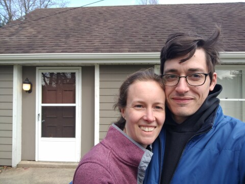 My wife and I standing in front of our hold house on our last night there.